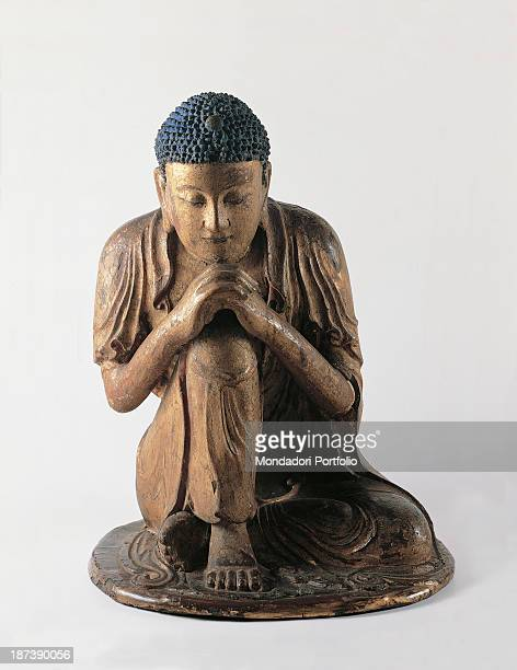 Italy Lazio Rome Palazzo Koch All A kneeling Buddha absorbed in meditation with his hands united in a prayer gesture The wooden statue keeps its...