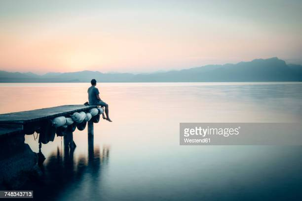 italy, lazise, man sitting on jetty looking at lake garda - kalmte stockfoto's en -beelden
