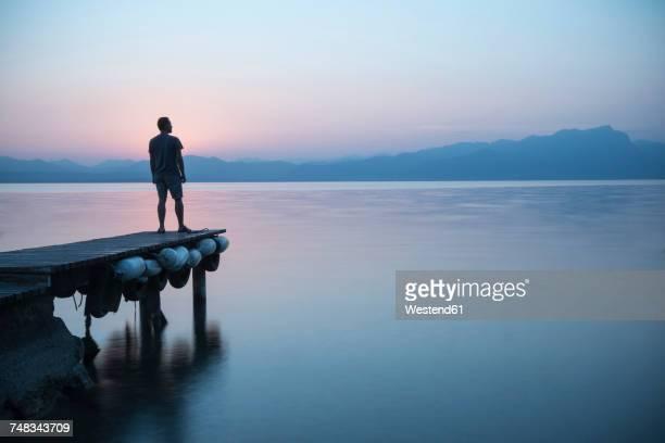 Italy, Lazise, man standing on jetty looking at Lake Garda
