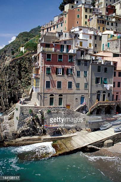 Italy Liguria Cinque Terre Riomaggiore Cluster Of Houses On Ocean Coastline Little Boats On Pier