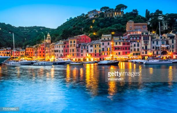 italy, liguria, portofino, boats in harbour at blue hour - portofino stock pictures, royalty-free photos & images