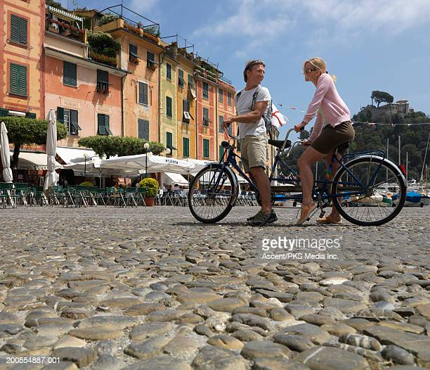 italy, liguria, portofino. couple riding tandem bicycle in street - liguria foto e immagini stock