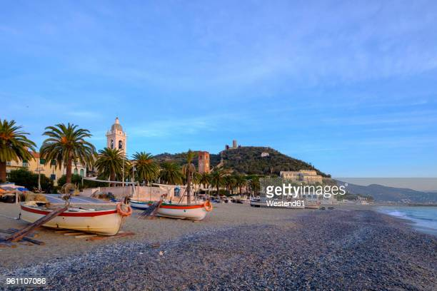 italy, liguria, riviera di ponente, noli, fishing boats at beach in the morning light - liguria stock photos and pictures