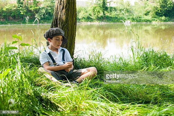 Italy, little boy wearing vintage clothing leaning against tree trunk