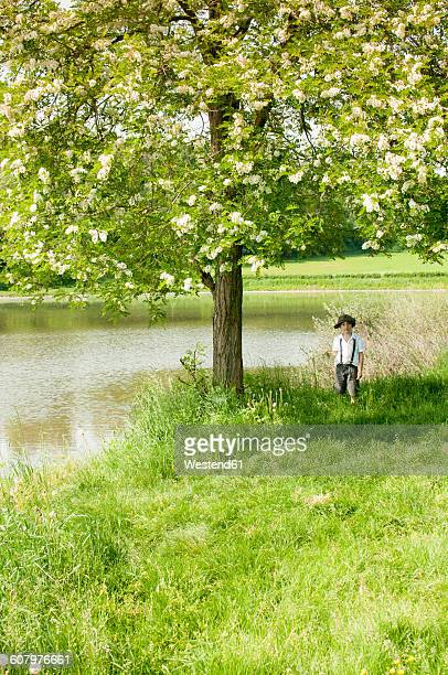 Italy, little boy wearing vintage clothing standing under a tree