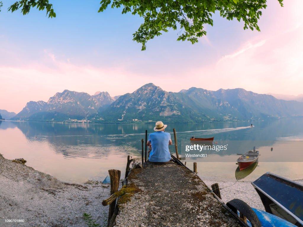 Italy, Lombardy, back view of man sitting on jetty at Lake Idro at morning twilight : Stockfoto