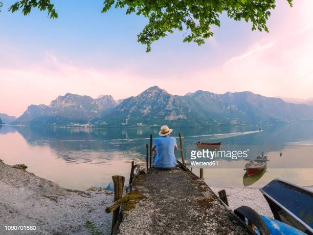 italy, lombardy, back view of man sitting on jetty at lake idro at morning twilight - travel foto e immagini stock