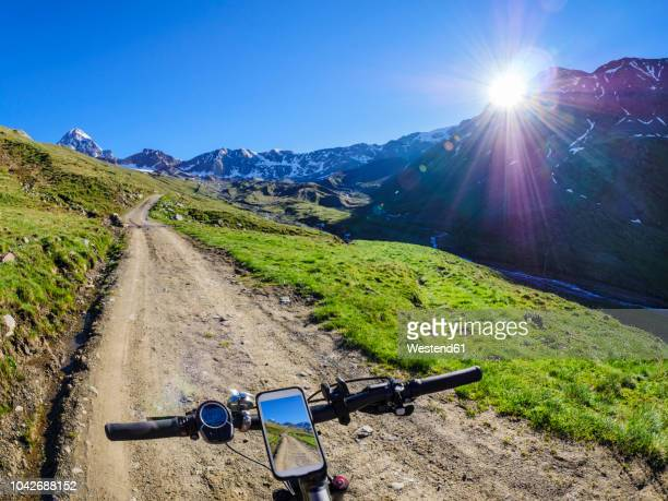 Italy, Lombardy, Cevedale Vioz mountain crest, cell phone on mountain e-bike
