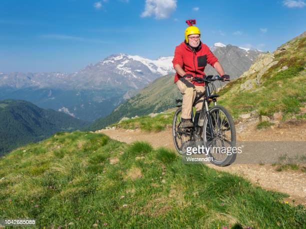 Italy Lombardy, Passo di Val Viola, Man riding e-bike in the mountains with action cam on his helmet