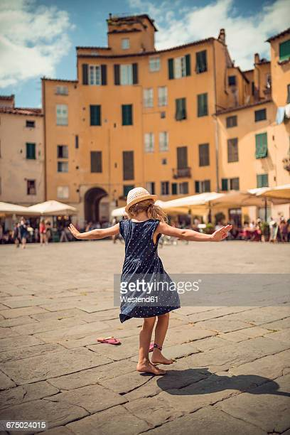 Italy, Lucca, back view of little girl dancing at the Piazza dellAnfiteatro
