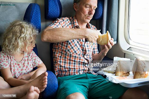 Italy, man eating bread in train while girl watching