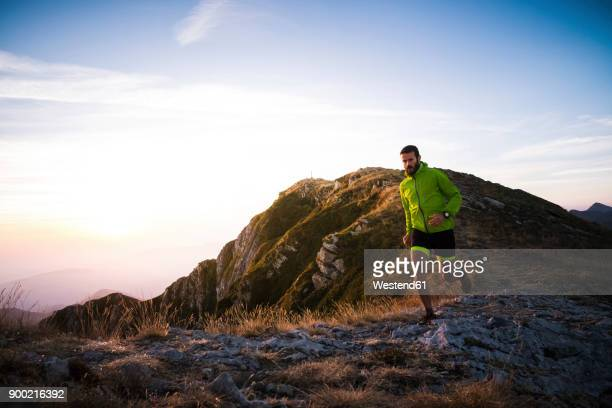 italy, man running on mountain trail - jacket stock pictures, royalty-free photos & images