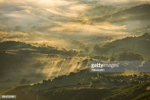 Italy, Marche, Apennines, aerial view of valleys with fog at sunrise