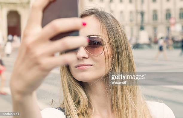 Italy, Milan, blond tourist with sunglasses taking selfie in front of Milan Cathedral