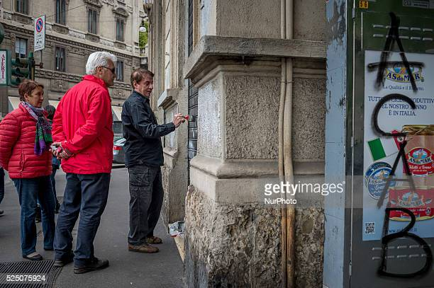Citizens do fake to clean up graffiti left on the walls of Milan against EXPO 2015 on May 3, 2015 as part of a civilian action against the damage...