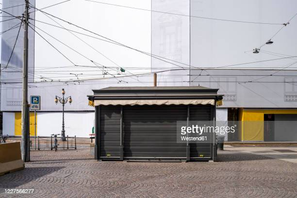 italy, milan, closed booth at piazza cordusio during covid-19 outbreak - industrial door stock pictures, royalty-free photos & images