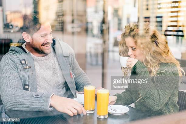 Italy, Milan, couple in love sitting in a coffee shop having fun
