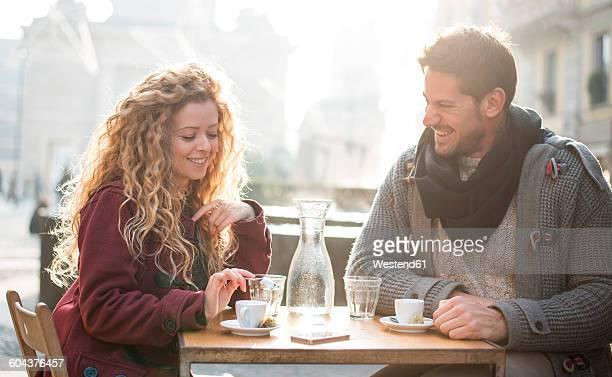 Italy, Milan, couple sitting at sidewalk cafe having fun