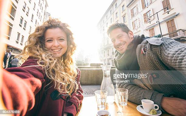 Italy, Milan, couple sitting at sidewalk cafe taking selfies
