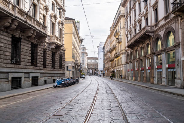 Italy, Milan, Railroad tracks stretching along empty city street during COVID-19 outbreak
