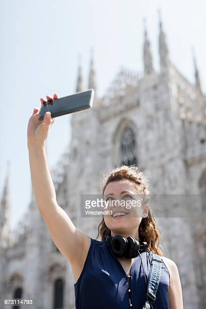 Italy, Milan, tourist taking selfie with cell phone in front of cathedral