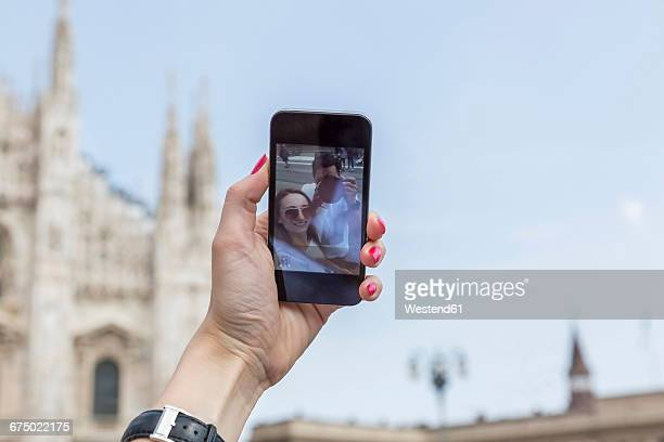 Italy, Milan, tourist taking selfie with smartphone, close-up