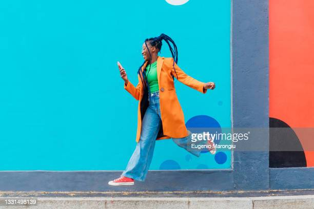 italy, milan, woman with braids jumping against blue wall - multi colored shoe stock pictures, royalty-free photos & images