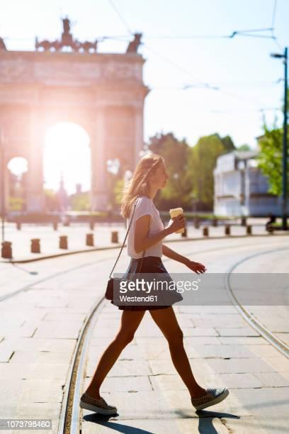 italy, milan, young woman walking in the city - mulher saia curta imagens e fotografias de stock