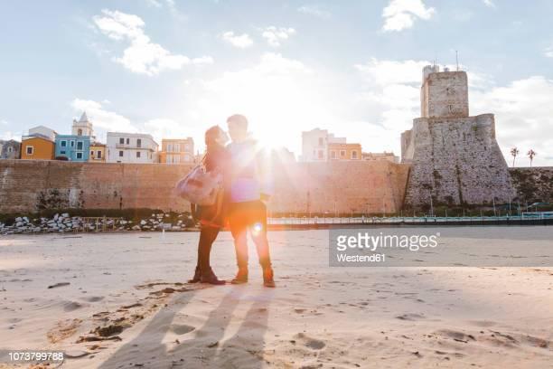 italy, molise, termoli, young couple in the beach at sunrise - molise foto e immagini stock