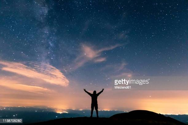 italy, monte nerone, silhouette of a man looking at night sky with stars and milky way - bras en l'air photos et images de collection