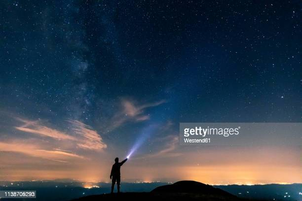 italy, monte nerone, silhouette of a man with torch under night sky with stars and milky way - position stock-fotos und bilder