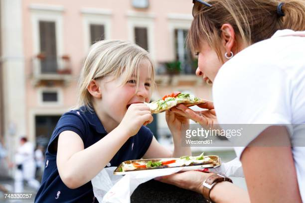Italy, mother and little daughter eating Pizza together