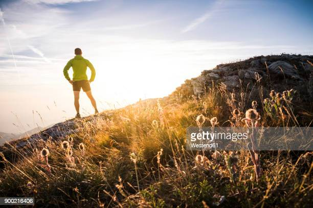 italy, mountain running man standing on trail looking at sunset - motivation stock pictures, royalty-free photos & images