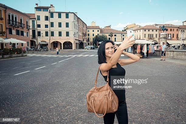 Italy, Padua, Young woman taking selfie