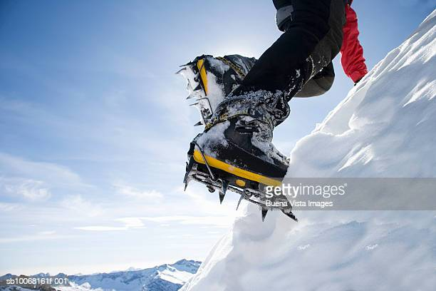 Italy, Piedmont, Alps, man wearing ice climbing crampons, low section, close-up