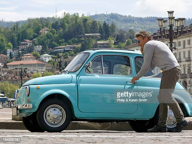 italy, piedmont, turin, man entering vintage car - 入る ストックフォトと画像