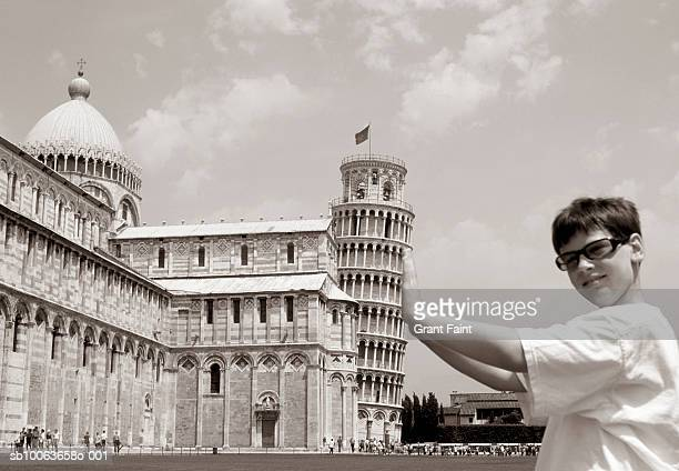 Italy, Pisa, boy (12-13) photographed as if holding up Leaning Tower of Pisa, portrait
