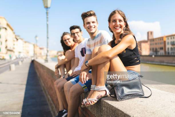 italy, pisa, group of four happy friends sitting on a wall along arno river - vier personen stockfoto's en -beelden