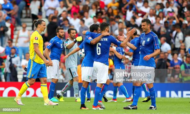 Italy players celebrate their win as Sweden's Zlatan Ibrahimovic leaves the pitch after the final whistle