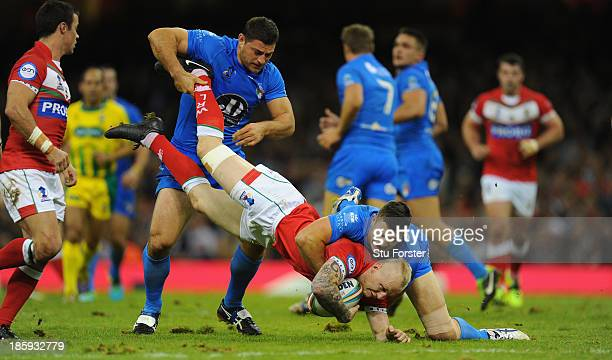Italy players Mark Minichello and Joshua Mantellato combine to halt Wales player Rhys Evans during the Rugby League World Cup Inter-group Match...