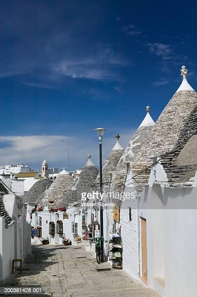 italy, puglia, alberobello, street lined with trulli houses - alberobello foto e immagini stock