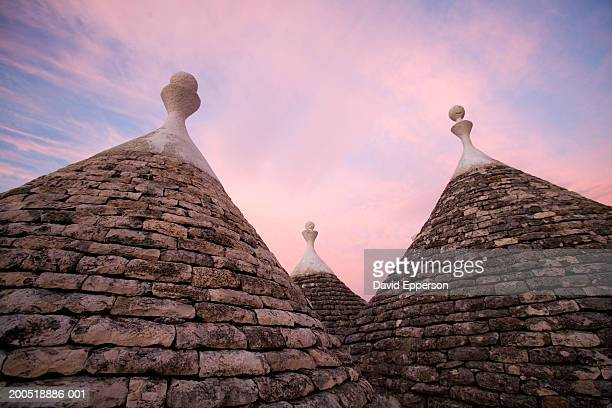 italy, puglia, cisternino, trulli at sunset, low angle view - trulli stock photos and pictures
