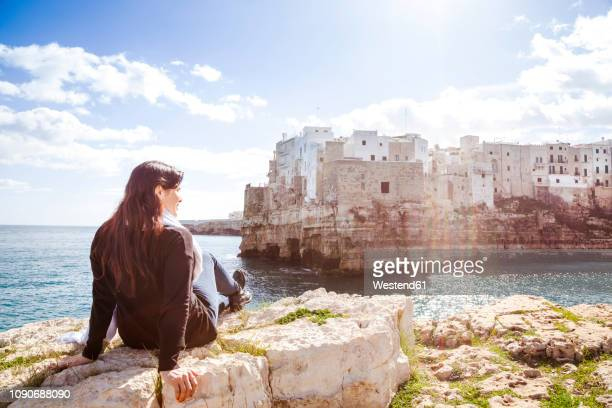 Italy, Puglia, Polognano a Mare, back view of woman relaxing on rocks looking at historic old town
