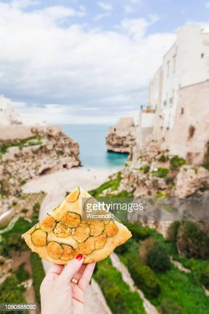 italy, puglia, polognano a mare, woman's hand holding piece of zucchini focaccia - les pouilles photos et images de collection
