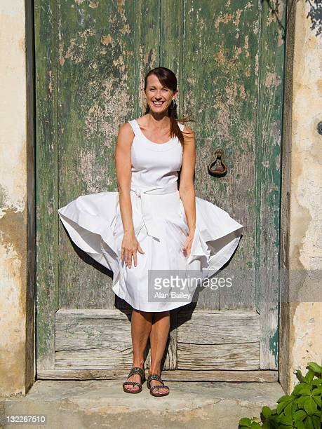 italy, ravello, portrait of woman standing in front of watered wooden door, wind blowing woman's dress - abito senza maniche foto e immagini stock