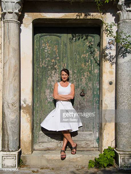 italy, ravello, portrait of woman standing in front of watered wooden door - abito senza maniche foto e immagini stock