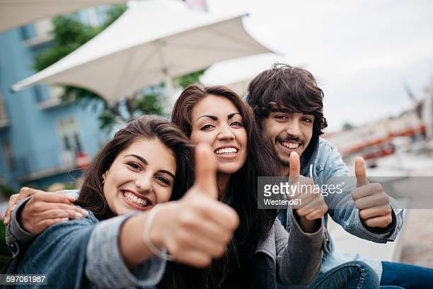 Italy, Rimini, portrait of three happy friends outdoors with thumbs up