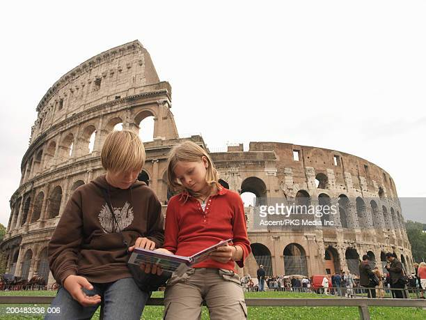 Italy, Rome, children (9-14) looking at guidebook