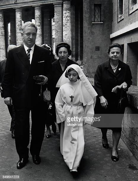 Italy Rome girl dressed in white dress and her parents going to the First Holy Communion