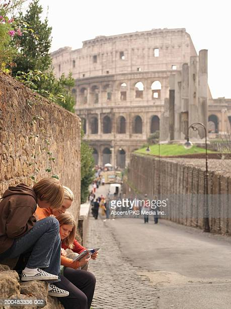 italy, rome, mother and children (9-14) checking guidebook - rome italy stock pictures, royalty-free photos & images